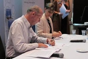 Image shows, left to right, Jonathan Loraine, Chair, CRC ORE, Elizabeth Lewis-Gray, Chair, Austmine and Christine Gibbs Stewart, CEO, Austmine, signing and witnessing the MoU between Austmine and CRC ORE. Image credit: Austmine