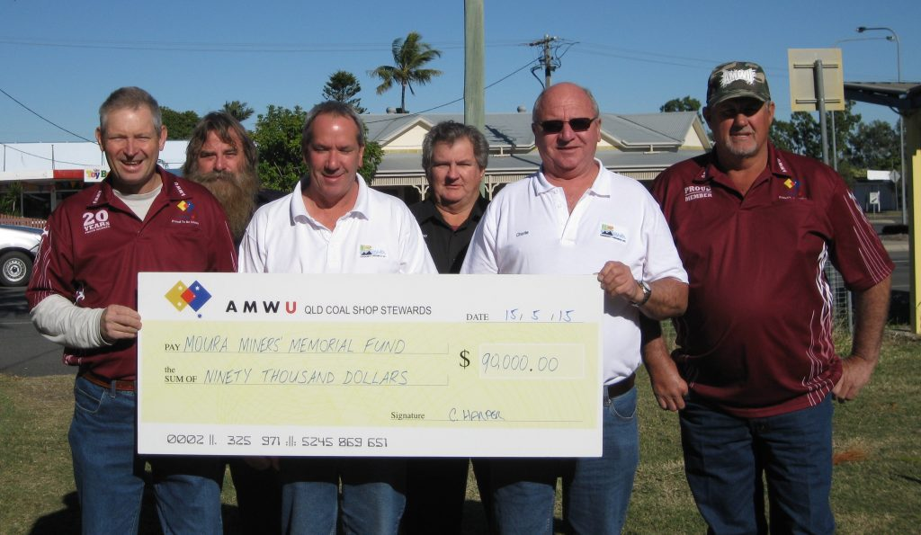 Chris Harper, Peter Lyon, John Walker, John Hempseed, Charlie Seeney and Peter Hammond with the symbolic AMWU cheque on the site in Moura where the memorial will be built Image credit: www.amwu.org.au